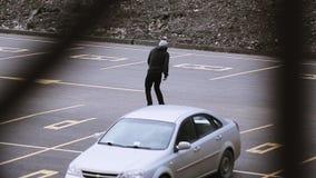 El skater joven en el montar a caballo del sombrero en espacio de estacionamiento, hace tirones Manía extrema almacen de video