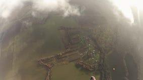 El Skydiver abre el paracaídas en cielo sobre campos verdes Actividad extrema adrenalina almacen de video