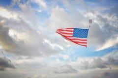 El skydiver a solas lleva una bandera americana contra un cielo nublado imagenes de archivo