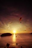 El Skydiver vuela sobre el mar en el fondo de la vertical de la puesta del sol foto de archivo