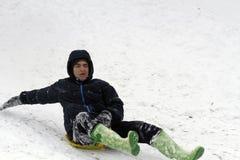 El Sledding abajo de las colinas en un día de invierno Foto de archivo