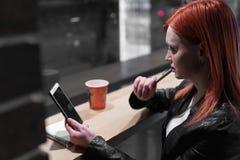 El smartphone de la tenencia de la muchacha a disposici?n, se sienta en el caf?, funcionamiento, pluma, artilugio del uso Red, wi fotos de archivo