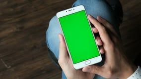 El smartphone del control de las manos del hombre con greenscreen la exhibición almacen de metraje de vídeo