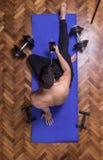 El smartphone relajante del hombre joven elevó la estera del ejercicio de la visión Foto de archivo libre de regalías