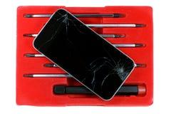 El smartphone y los destornilladores agrietados fijaron aislado en el fondo blanco Fotografía de archivo