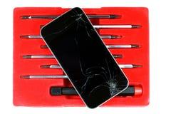 El smartphone y los destornilladores agrietados fijaron aislado en el fondo blanco Imágenes de archivo libres de regalías