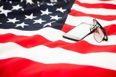 El smartphone y los vidrios negros están en la bandera de los E.E.U.U. Foto de archivo libre de regalías