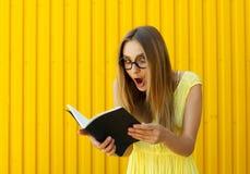 El smiley bonito sorprendió a la estudiante con el libro que llevaba el juguete divertido Fotos de archivo