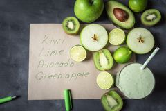 El smoothie sano con las frutas verdes y los ingredientes enumeran sobre v fotos de archivo