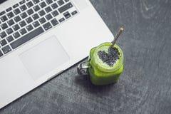 El smoothie verde fresco con el plátano y la espinaca con el corazón de semillas de sésamo y de un ordenador portátil aman para u Imagen de archivo libre de regalías