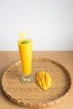 El smoothie y el mango frescos del jugo del mango dan fruto con la cesta de bambú Fotos de archivo