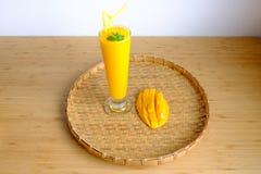 El smoothie y el mango frescos del jugo del mango dan fruto con la cesta de bambú Fotografía de archivo libre de regalías
