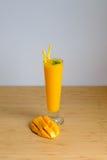 El smoothie y el mango frescos del jugo del mango dan fruto con la cesta de bambú Foto de archivo