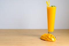 El smoothie y el mango frescos del jugo del mango dan fruto con la cesta de bambú Imagenes de archivo