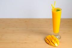 El smoothie y el mango frescos del jugo del mango dan fruto con la cesta de bambú Foto de archivo libre de regalías