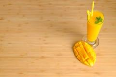 El smoothie y el mango frescos del jugo del mango dan fruto con la cesta de bambú Fotografía de archivo
