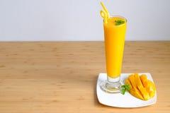 El smoothie y el mango frescos del jugo del mango dan fruto con la cesta de bambú Imagen de archivo
