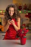 El SMS de la escritura de la mujer en la Navidad adornó la cocina Imagenes de archivo