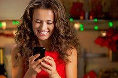 El SMS de la escritura del ama de casa en la Navidad adornó la cocina Imágenes de archivo libres de regalías