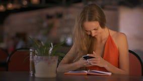 El SMS de los textos de la muchacha al amigo utiliza el móvil en la tabla del café almacen de metraje de vídeo