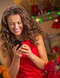 El SMS joven feliz de la escritura del ama de casa en la Navidad adornó la cocina Imagen de archivo