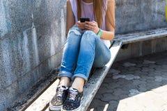 El SMS que manda un SMS de la muchacha joven del estudiante y se relaja en parque de la ciudad Imagen de archivo