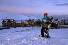 El snowboarder bonito de la muchacha se coloca en el frente de la estación de esquí del hotel Foto de archivo