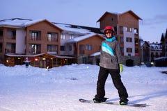 El snowboarder bonito de la muchacha se coloca en el frente de la estación de esquí del hotel Fotografía de archivo