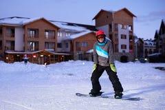 El snowboarder bonito de la muchacha se coloca en el frente de la estación de esquí del hotel Imagenes de archivo