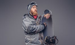 El snowboarder brutal del pelirrojo con una barba llena en un sombrero y vidrios protectores del invierno se vistió en una capa d imagen de archivo libre de regalías