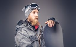 El snowboarder brutal del pelirrojo con una barba llena en un sombrero y vidrios protectores del invierno se vistió en una capa d foto de archivo libre de regalías