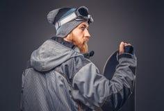 El snowboarder brutal del pelirrojo con una barba llena en un sombrero y vidrios protectores del invierno se vistió en una capa d fotografía de archivo libre de regalías
