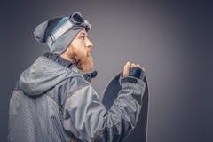 El snowboarder brutal del pelirrojo con una barba llena en un sombrero y vidrios protectores del invierno se vistió en una capa d imagenes de archivo