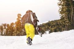 El snowboarder cansado va en cuesta del esquí Foto de archivo
