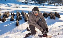 El Snowboarder coloca el top de la montaña, abotonando la cerradura para una snowboard Imagenes de archivo