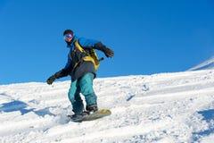 El snowboarder de Freeride rueda en una cuesta nevada que se va detrás de un polvo de la nieve contra el cielo azul Fotos de archivo