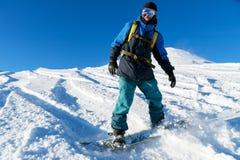 El snowboarder de Freeride rueda en una cuesta nevada que se va detrás de un polvo de la nieve contra el cielo azul Foto de archivo