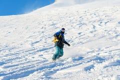 El snowboarder de Freeride rueda en una cuesta nevada que se va detrás de un polvo de la nieve contra el cielo azul Fotografía de archivo libre de regalías