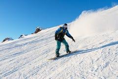 El snowboarder de Freeride rueda en una cuesta nevada que se va detrás de un polvo de la nieve contra el cielo azul Imagen de archivo