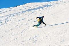 El snowboarder de Freeride rueda en una cuesta nevada que se va detrás de un polvo de la nieve contra el cielo azul Imagenes de archivo