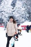 El snowboarder de la muchacha en la madera del invierno Imagen de archivo