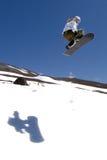 El snowboarder de la mujer salta la sombra Fotografía de archivo