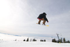 El Snowboarder de sexo masculino coge el aire grande. Foto de archivo