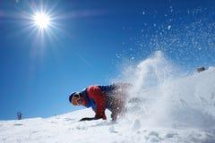 El snowboarder de sexo masculino del atleta se cae en nieve Foto de archivo libre de regalías