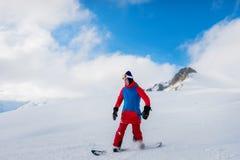 El snowboarder de sexo masculino elegante del atleta monta en una pizarra en el sn Foto de archivo libre de regalías