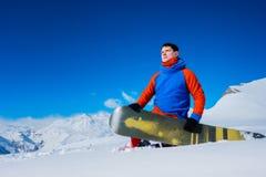 El snowboarder de sexo masculino elegante del atleta se sienta en la nieve Imagenes de archivo