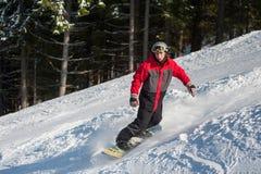 El snowboarder de sexo masculino resbala abajo de la montaña Fotos de archivo libres de regalías