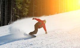 El snowboarder de sexo masculino resbala abajo de la montaña en día de invierno Imágenes de archivo libres de regalías