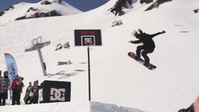 El snowboarder del lanzamiento del cameraman salta del trampolín detrás de cesta del baloncesto Dom metrajes