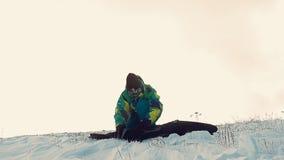 El Snowboarder en la snowboard de la montaña consigue almacen de video